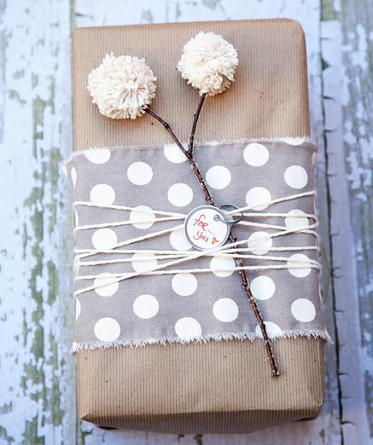 Envolver regalos con papel craft, pompon y tela.